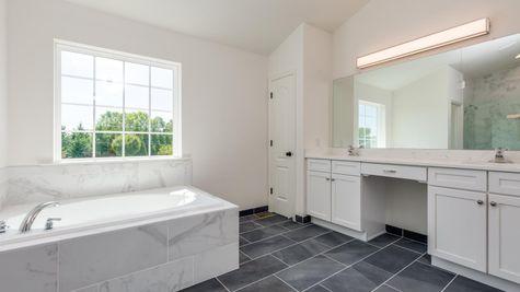 Baldwin master bath with soaking tub, large window, and large double sink vanity