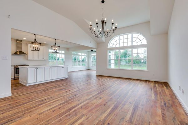 Interior of Avignon model new home with wood floors, white walls, chandeliers, family room to right, kitchen to left.