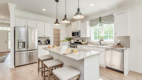 Kitchen in Zinnia model one story new home in south NJ with white cabinets, three pendant lights over center island,