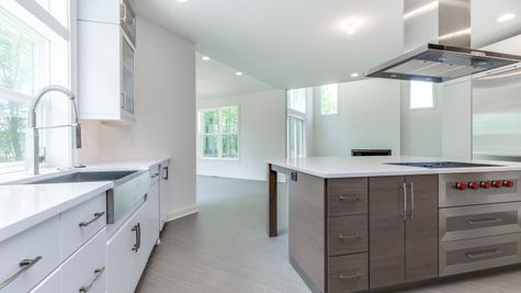 The Stoneleigh gourmet kitchen with white cabinets and stainless steel appliances.