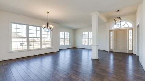 Avignon one story new home with open floor plan living room & dining room area, white walls, wood floors, many windows.