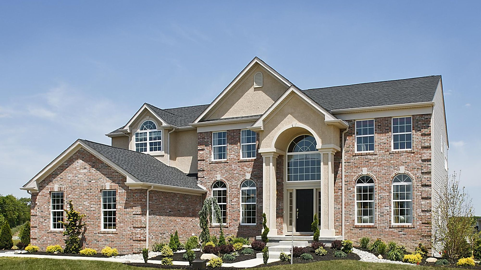 Oxford Traditional luxury new home in south Jersey with brick front, 2 story columns, peaked roof and palladian window over door, 2 car garage.