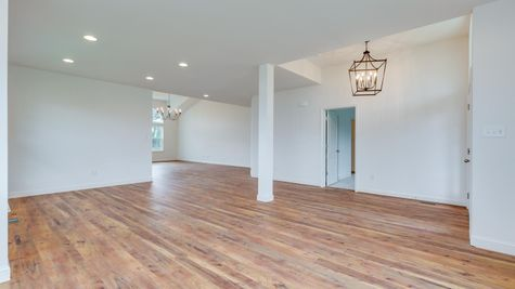 Interior of Avignon model new home with white walls, wood floors, two chandeliers, open floorplan.