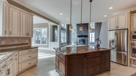 Stoneleigh Kitchen with center island, pendant lights over island, tile floor, granite counters, light color cabinets.