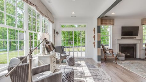 Morning room with many windows and family room in background with fireplace, wood floors, white walls in Zinnia new home.