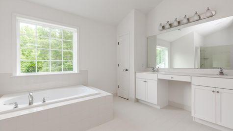 Baldwin master bathroom with soaking tub, large double sink vanity and large window over tub