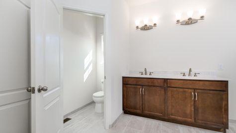 Bathroom with double sinks vanity in Avignon model new home, wood vanity.