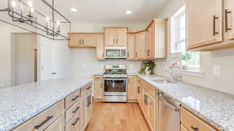 Kitchen in the Primrose model new home for age 55+ active adults, with blond wood cabinets, granite counters, island.