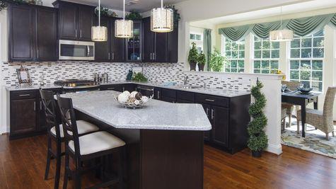 Baldwin model home kitchen with island, granite countertops, dark cabinets, pendant lights over island.