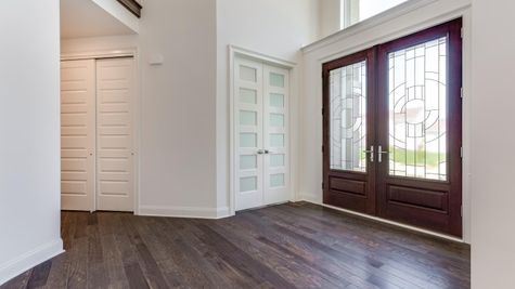 Entry Hall of The Stoneleigh luxury new home in NJ, featuring double front door with glass inserts, wood floor, coat closet to side.