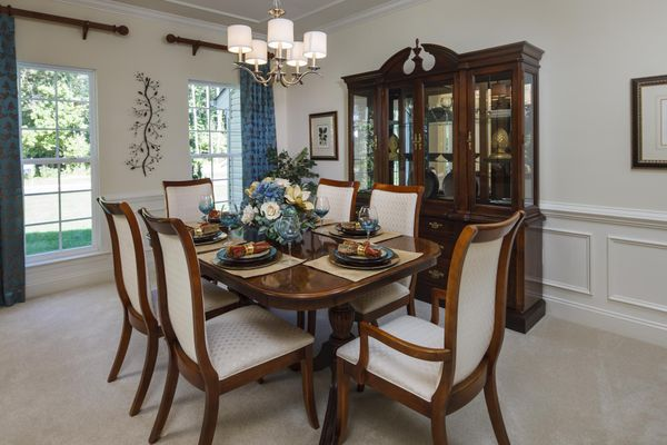 Baldwin model home formal dining room with two windows, central chandelier and sample furniture.