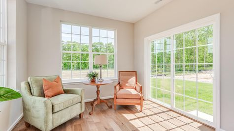 Primrose model new home sun room with many windows and sliding glass door to back yard.