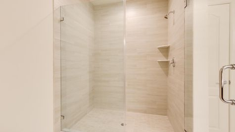 Walk in shower with light tile and glass doors in Magnolia model new home in southern NJ.