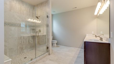 Bathroom in Magnolia model new home with walk-in shower and decorative tile, double sink vanity