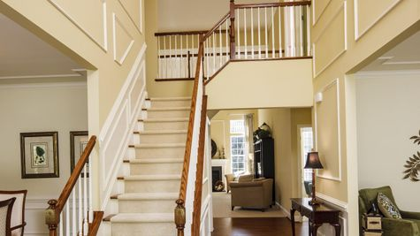 Stair case in front hall of Baldwin model new home, wood floors, open landing upstairs.