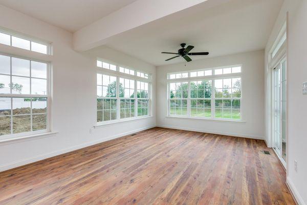 Avignon model home morning room option with many windows, white walls, wood floors.