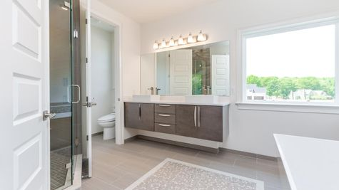 Stoneleigh Master Bathroom with large picture window, soaking tub, walk-in shower, double sink vanity, large mirror above.
