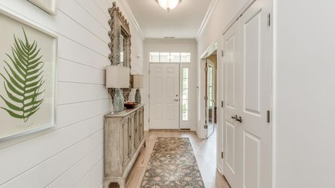 Front Entry of the Zinnia decorated model one story new home with white walls, and sample home decor.