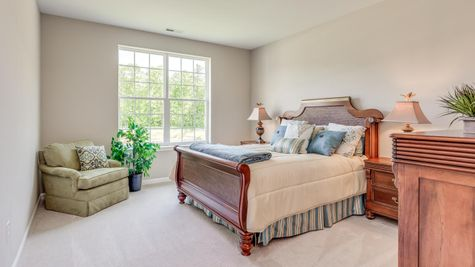 Primrose Master Bedroom with windows, carpet, sample furniture.