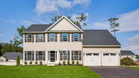 A Wexford Federal style new home in NJ with cream siding, dark shutters and door, central peak on roofline.
