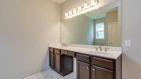 Double sink vanity in Magnolia model new home with very large mirror