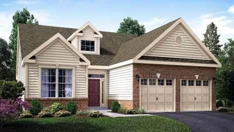 The Magnolia Manor one story ranch new home in NJ with brick surrounding 2 garage doors, tan siding and colonial trim.