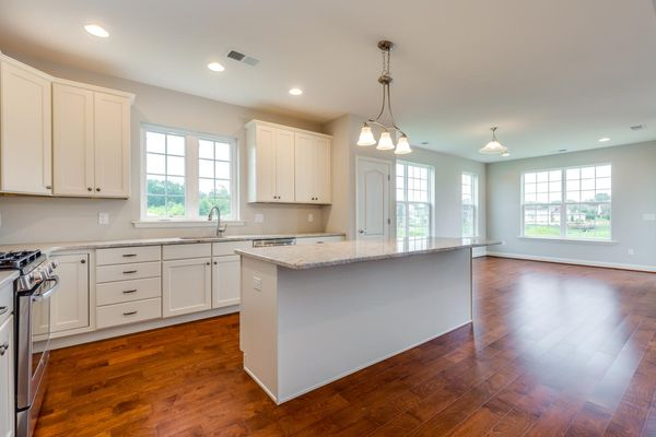 Kitchen and eating area in Magnolia model new home, one story ranch style, with white cabinets and wood floors.