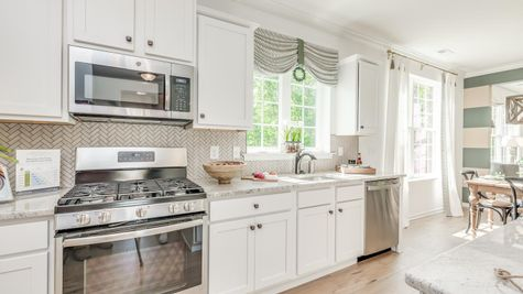 Kitchen in Zinnia model home with white cabinets, wood floors, stove + oven with microwave above.