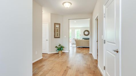 Primrose model one story active adult home, front hall with view of the great room in the background, wood floors.