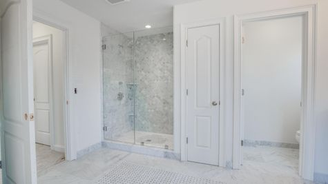 Shower in Brandywind master bathroom with decorative tile and glass doors.
