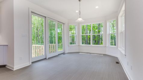The Stoneleigh optional morning Room, with many windows and central white hanging light fixture, sliding doors to outside