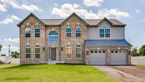 The Baldwin Georgian style model luxury new home in NJ offers twin peaked roof line, brick front and arched windows.