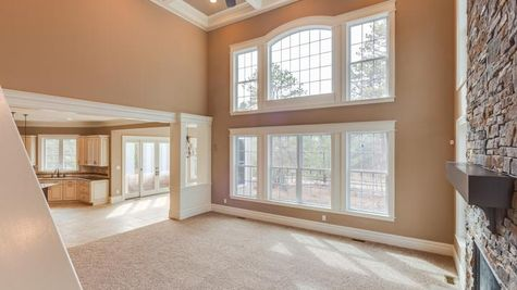Two story family room of the Stoneleigh model new home with stone fireplace and large set of two story high windows.
