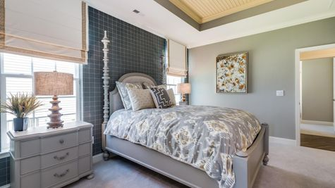 Hawthorn model home master bedroom with sample furniture and carpet.