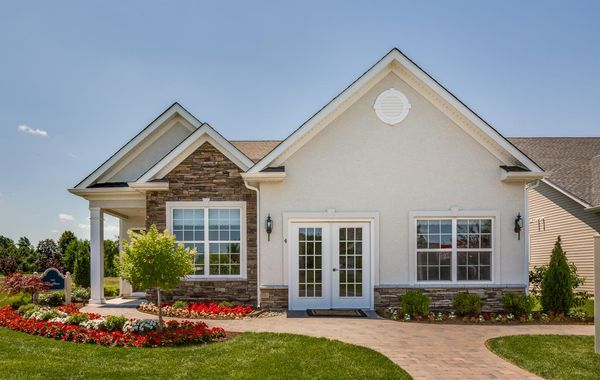 Exterior of the sales office at Village of Country Gardens, cream stucco & light brown stone, a 55+ active adult community in South Jersey, Hawthorn Villa model.