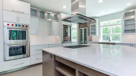 Stoneleigh Gourmet Kitchen with double wall oven, large cook top & large stainless steel exhaust hood, white cabinets.