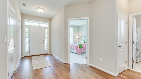 Interior view of the front door, front hall and bedroom to the right, wood floor, white walls, windows around front door.