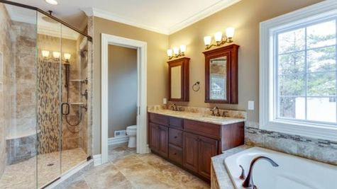 The Stoneleigh Master Bathroom with soaking tub, walk-in shower with glass door, double sink vanity with mirrored cabinets above.