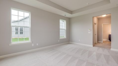 Bedroom in Magnolia model home with pale carpet, white walls, two windows.
