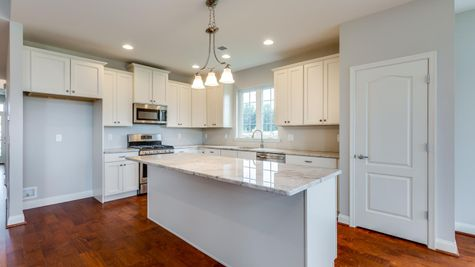 Kitchen in Magnolia one story home in South NJ with white cabinets, granite counters, and hardwood floor.