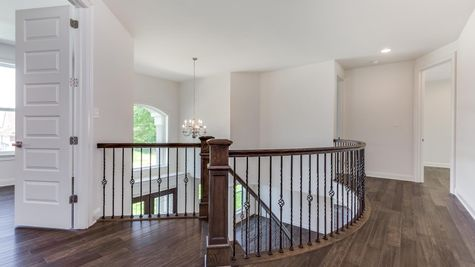 The Stoneleigh second floor landing area and hall, with view of two story entry hall and chandelier.