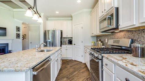 Hawthorn kitchen with white cabinets, granite counters, island with pendant light, open to family room.