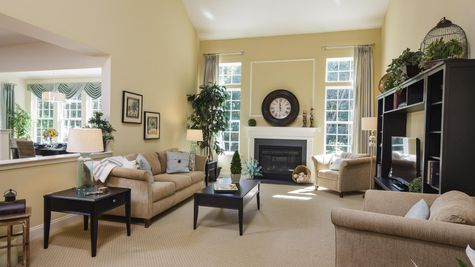Baldwin model home two story family room next to kitchen with fireplace and double height windows beside it.
