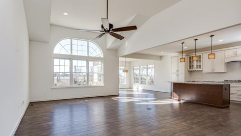 Family room of Avignon one story model home with large arched window and kitchen to the side, plus morning room,