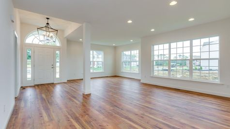 Front entry and living area of one story Avignon model new home in NJ with wood floors, white walls, many windows.