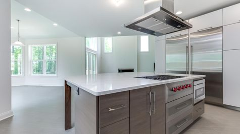 The Stoneleigh kitchen with large center island in foreground, large Subzero refrigerator to left, stainless steel exhaust hood.