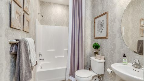 Hall bathroom in Zinnia model new home with pedestal sink and shower over tub.
