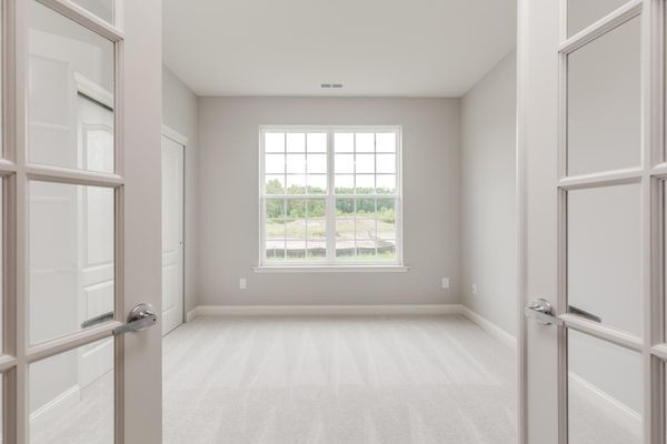 The home office in the one story Magnolia model home, painted white with windows, carpet and double doors.