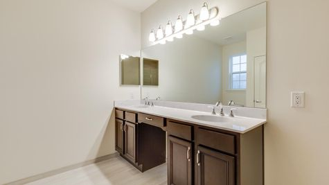 Double sink vanity in Magnolia model new home with very large mirror, lights over mirror.