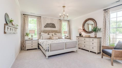 Master bedroom in Zinnia model new home with pale carpets, three large windows and sample furniture.